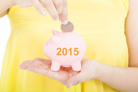 young add: hand putting coin into a piggy bank for 2015 investment concept Stock Photo