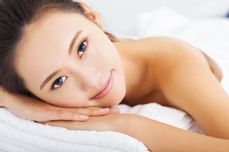 lying on side: Young  smiling woman getting spa treatment over white background Stock Photo