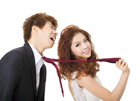 bride pulling on groom tie for control concept Stock Photo