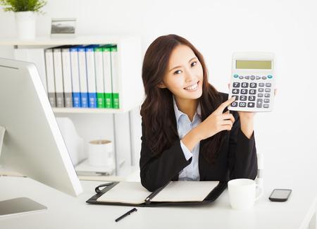 calculadora: mujer de negocios inteligente que muestra la calculadora en la oficina