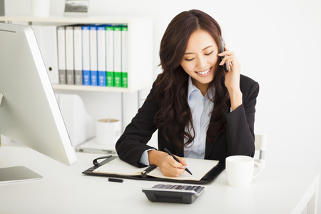 phones: happy young businesswoman working in the office Stock Photo