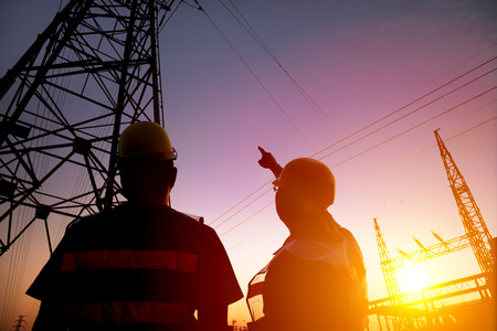 seguridad industrial: dos trabajadores de ver la torre de energía y de la subestación con el fondo de la puesta del sol Foto de archivo