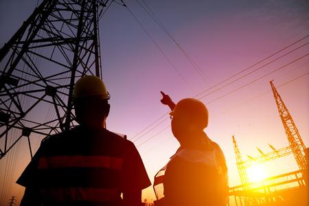 dwa pracownik oglądania wieża zasilania i podstacji z tle zachodu słońca