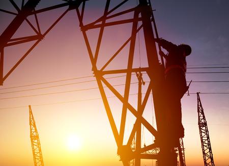 climber: Werknemer bij een elektrisch onderstation met zonsondergang op de achtergrond Stockfoto