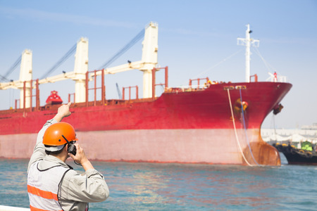 hard look: Harbor dock worker talking on  radio with ship background