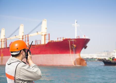 trabajando duro: Harbor trabajador portuario hablando en la radio con el fondo barco
