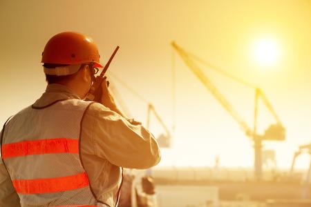 werknemer met een grote kraan ter plaatse en zonsondergang op de achtergrond