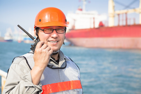 commercial docks: smiling dock worker holding  radio and  ship background