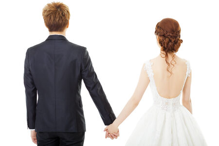 Back view of holding hands bride and groom isolated on white Stock Photo