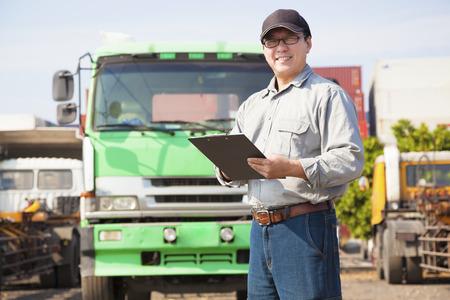 ciężarówka: szczęśliwy kierowca ciężarówki pisania na dokumencie Zdjęcie Seryjne