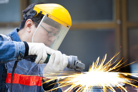 worker with grinder machine cutting metal in factory photo