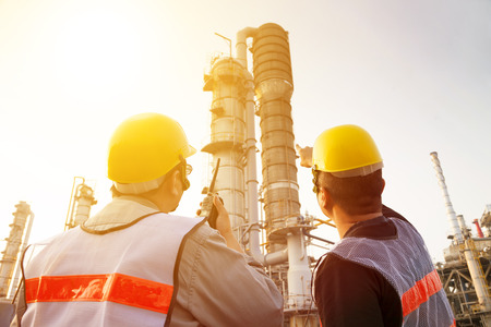 refinería de petróleo: trabajadores de las refinerías de discusión y apuntando para la inspección