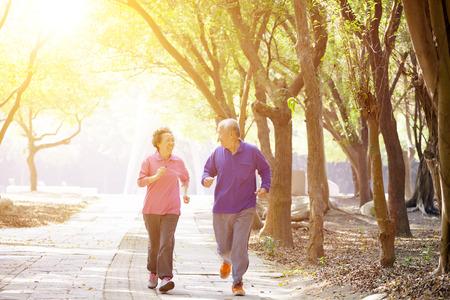 jubilados: feliz pareja mayor que ejercita en el parque Foto de archivo