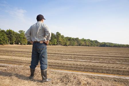 agricultor: Granjero que se coloca en la tierra de cultivo Foto de archivo