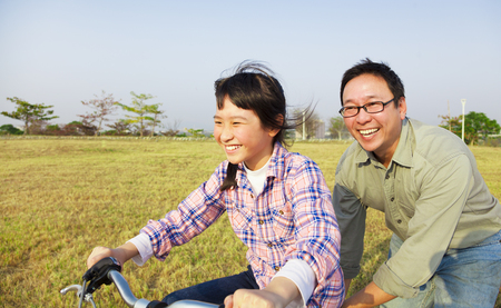father teaching daughter: happy Father teaching child to ride bicycle