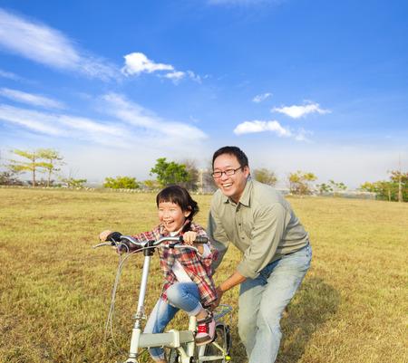 ni�os en bicicleta: feliz padre ense�anza de la ni�a a montar bicicleta