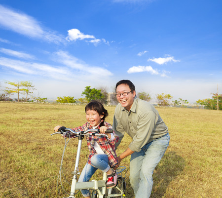 dad and daughter: happy Father teaching little girl to ride bicycle Stock Photo