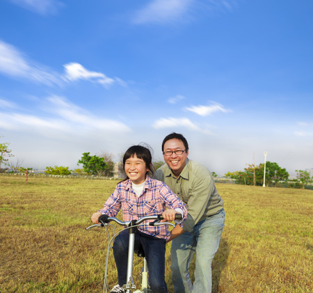 happy Father teaching his daughter to ride bicycle photo