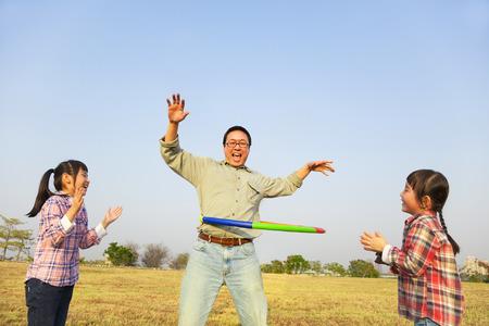 gelukkige familie spelen met hoelahoep buiten Stockfoto