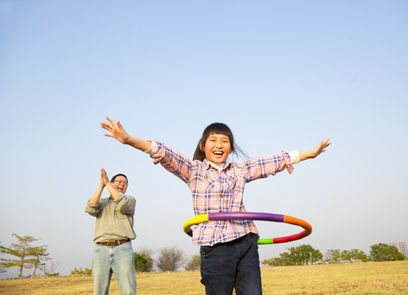 happy kid playing  hula hoops outdoors Stock Photo