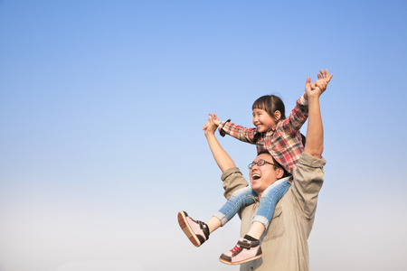 dad and daughter: happy Father carrying his daughter on shoulders with blue sky background