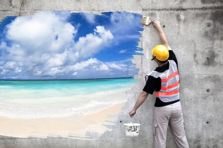 worker with paint brushes drawing summer beach on the wall photo