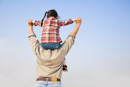 Father carrying his daughter on shoulders with blue sky background