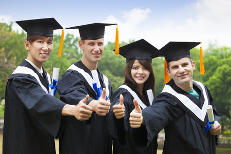 graduacion de universidad: estudiantes felices en vestidos de graduación que muestran diplomas con los pulgares arriba Foto de archivo