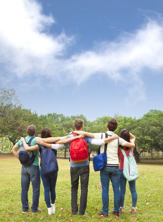 Joven grupo feliz de estudiantes mirando el cielo