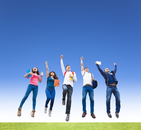 Happy young group of students jumping together Stock Photo