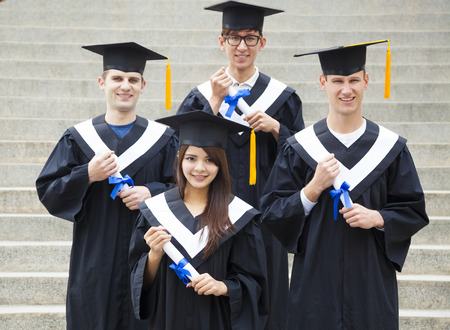 college graduation: young students in graduation gowns on university campus Stock Photo