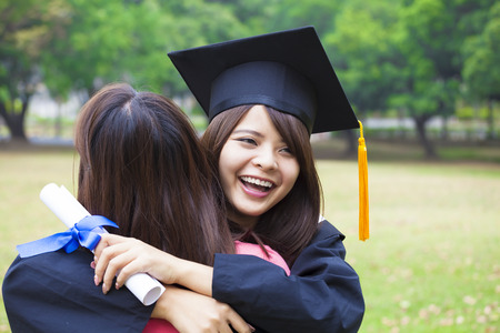 young female graduate hugging her friend at graduation ceremony 스톡 콘텐츠