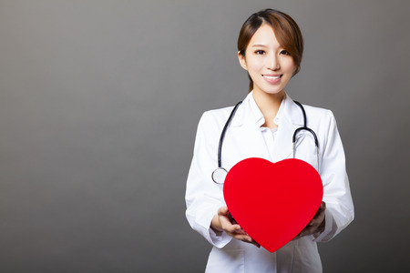 smiling asian female doctor with heart