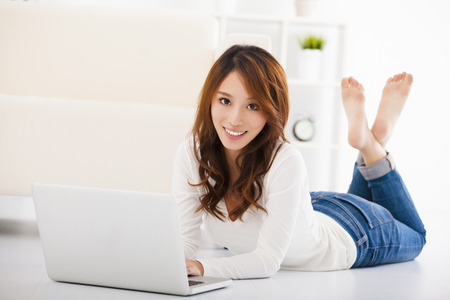 woman sitting floor: smiling Young woman  with laptop Stock Photo