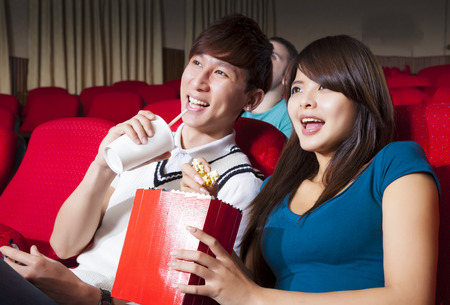 watch: Young couple  watching a movie at the cinema Stock Photo