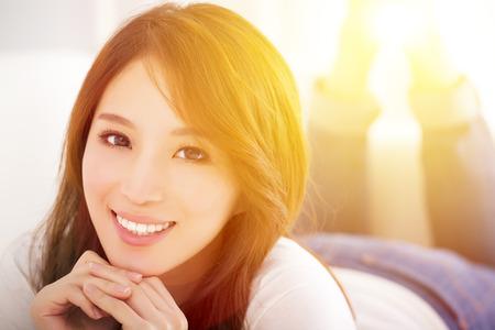 lifestyle: lächelnd Junge Frau auf dem Sofa mit Sonnenlicht Hintergrund liegen