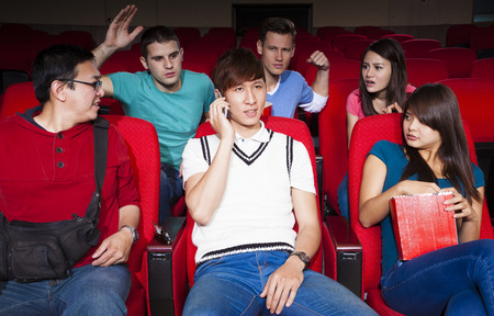 disrespectful: Young men talking on the phone while watching movie at the cinema