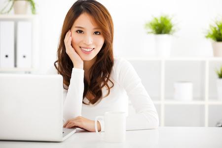visage: souriante jeune femme asiatique avec un ordinateur portable