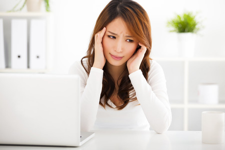 headache pain: Stressed young woman with laptop