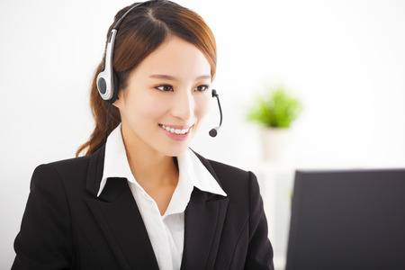 telephone headsets: young beautiful asian businesswoman with headset in office Stock Photo