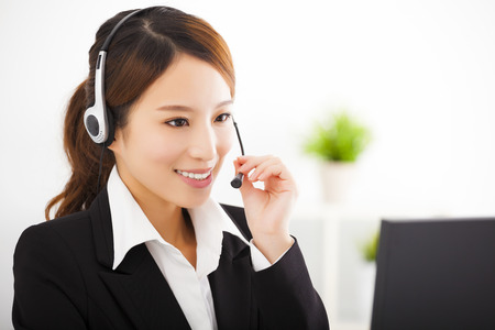 customer support: young beautiful businesswoman with headset in office Stock Photo