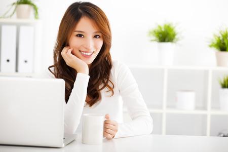 sorrisos: Mulher asi�tica de sorriso novo com o port�til