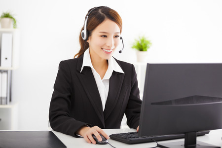 headphones: young beautiful asian businesswoman with headset in office Stock Photo