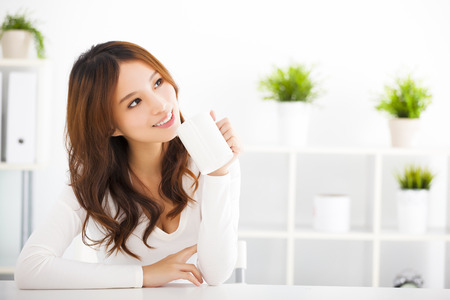 women holding cup: happy asian young woman drinking coffee