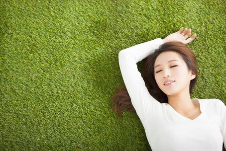 Ontspannen jonge vrouw, liggend op het gras