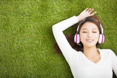 escuchar: Mujer Relaxed que escucha la m�sica con los auriculares que mienten en la hierba Foto de archivo