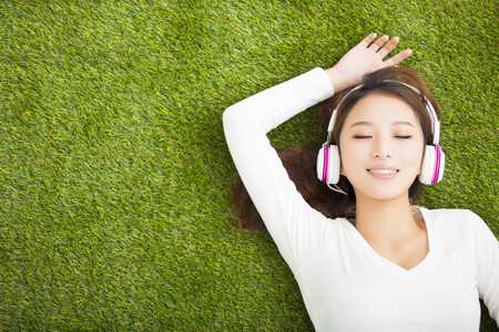 happy asian people: Relaxed woman listening to the music with headphones lying on the grass