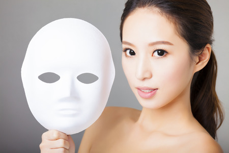 masks: young woman holding white mask for medical beauty concept