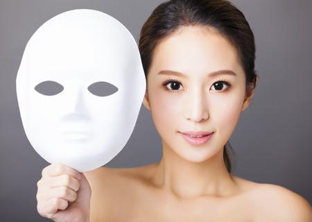 visage: jeune femme tenant de masque blanc pour concept de la beaut� m�dicale