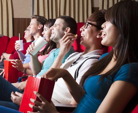 cinta pelicula: felices jóvenes miran una película en el cine
